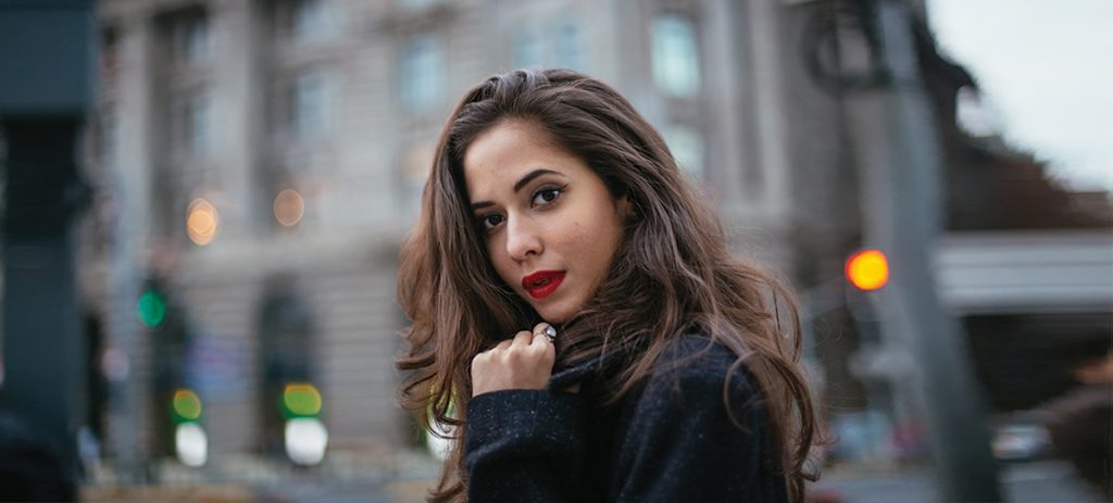 Brunette girl with red lipstick in the city