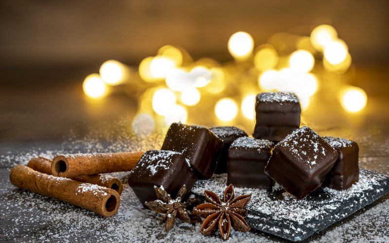 Kiel, Schleswig Holstein, Germany - October 9, 2018 : Christmas in Europe. Chocolate dominos, cinnamon and anise on wooden board with slate plate and candlelight.