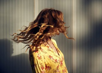 Germany, NRW, Cologne, red-haired woman throwing her hair in the evening sun, freedom